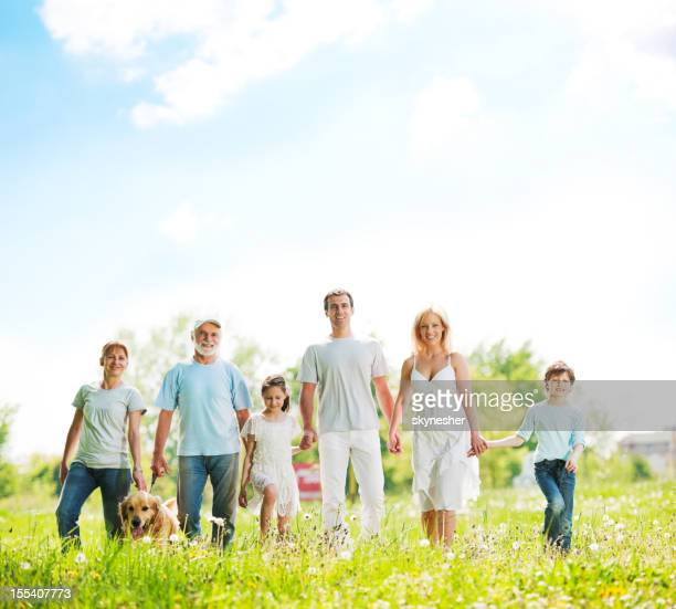 Large family with grandparents taking a walk in park.