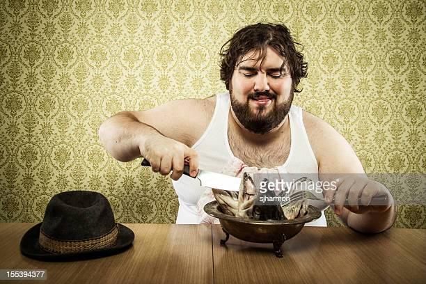 Grand gros homme manger la soupe de poisson de la tête sur une table en bois