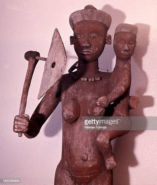 Large figure of a woman with the attributes of a chieftainess used to surmount the roof of a chiefs hut In addition to an axe of office and a cup she...