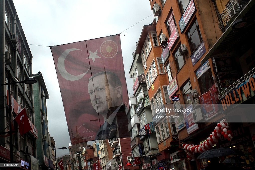A large flag of Turkish president Recep Tayyip Erdogan is seen hanging over a main street on October 25, 2016 in Rize Turkey. Although born in Kasimpasa, Istanbul, President Erdogan's family was originally from Rize a conservative town on the Black Sea. His family returned to Rize when Erdogan was very young staying until he was 13, before returning to Istanbul. Since the failed coup attempt on July 15, 2016 which saw 240 people killed including 173 civilians, Turkish authorities initiated a state of emergency, leading to an unprecedented crackdown on individuals and organizations with links to US-based cleric Fethullah Gulen and his organization blamed for instigating the uprising. The purge, targeting teachers, journalists, soldiers, judges, academics, police, military leaders, schools and universities has so far seen approximately 100,000 people dismissed, 70,000 detained, 32,000 arrested, 130 media outlets closed and some 15 universities shuttered. The failed coup and subsequent purge only appears to have further bolstered the president's popularity and increased nationalism across the country with July 15th having been marked as a new national holiday. Turkish flags, already prominently displaying all over have increased in numbers, as well as posters of those killed fighting the coup plotters appearing in train stations and public squares. The Bosphorus Bridge in Istanbul, which saw heavy fighting during the coup has been renamed the '15th July Martyr's Bridge'. These changes, follow a year of instability in the country with constant terrorist attacks, an economic downturn, plummeting tourism, and a refugee crisis, all contributing to Turkish society undergoing its most dramatic restructuring in decades.