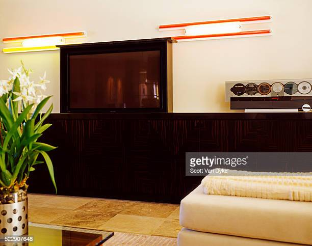 a large flat-screen television flanked by contemporary neon art centers a living room - 大型テレビ ストックフォトと画像