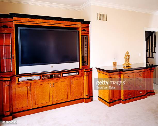 Large flat-screen tv is placed in a cabinet with a set of drawers beside it