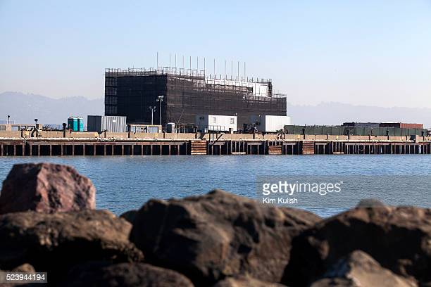 A large floating barge made of shipping containers apparently under construction is docked along a secured pier on Treasure Island in San Francisco...