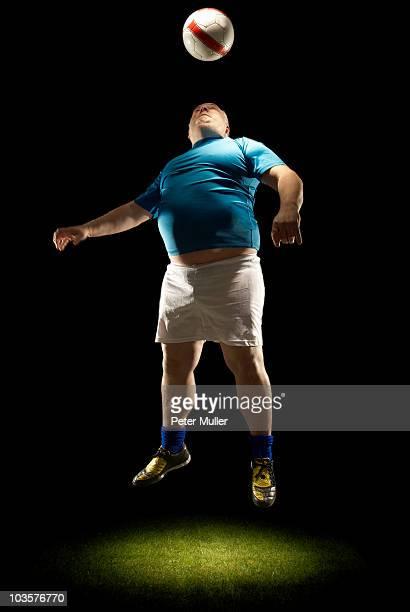 grandi calciatori professionisti colpire una palla - fat soccer players foto e immagini stock