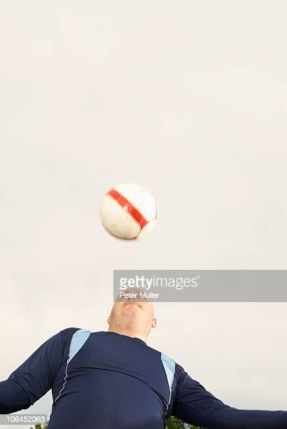 large footballer heading ball - fat soccer players foto e immagini stock