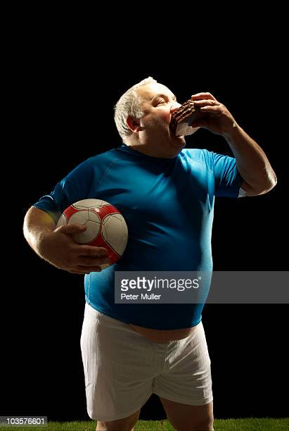 large footballer holding ball and eating - fat soccer players foto e immagini stock