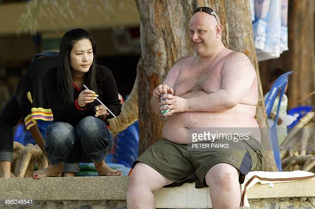A large foreign tourist take a drink from a Thai woman on Patong beach on the tsunamihit resort island of Phuket 23 January 2005 Phuket island's...