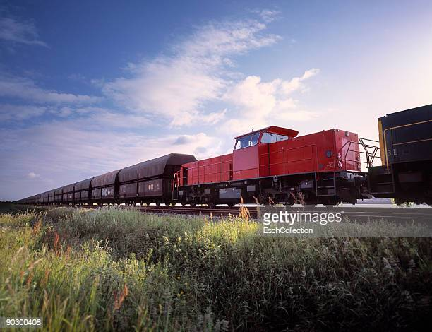 large freight train with red locomotive in front. - 貨物列車 ストックフォトと画像