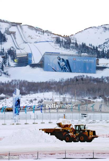 A large frontend loader removes snow from a parking lot at the Olympic Park site of several major events including the 120k and 90k ski jumps for the...