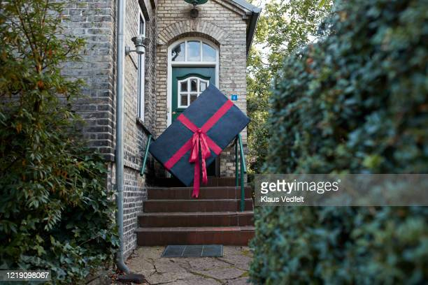 large gift box on steps of house - national holiday stock pictures, royalty-free photos & images