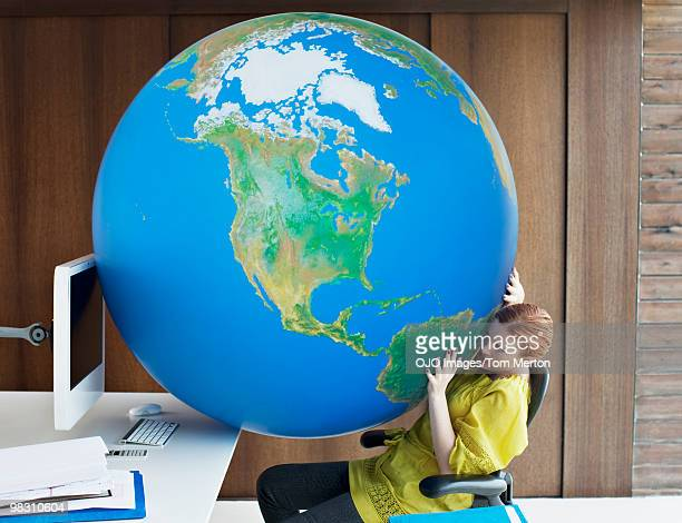 Large globe between businesswoman and computer in office