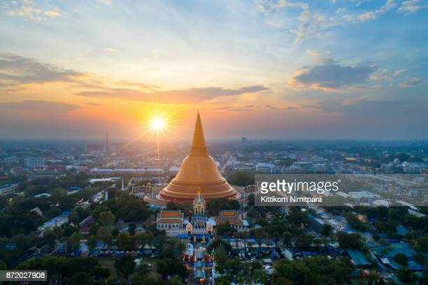 large golden pagoda located in the community at sunset , phra pathom chedi , nakhon pathom , thailand .the measure public.aerial view road roundabout with car lots in thailand.beautiful street. - stupa stock pictures, royalty-free photos & images