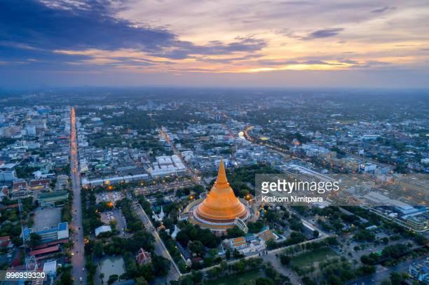 large golden pagoda located in the community at sunset , phra pathom chedi , nakhon pathom , thailand . - sukhothai stockfoto's en -beelden