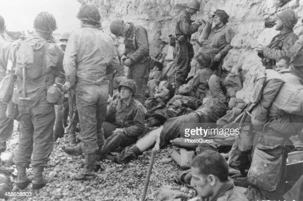 A large group of American assault troops take a breather behind the comparative safety of the chalk cliffs before moving inland ColvilleSurMer...
