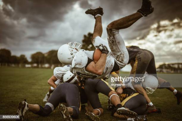 large group of american football players on a pile. - quarterback stock photos and pictures