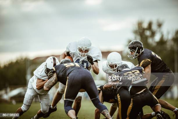 large group of american football players playing a match on a field. - wide receiver athlete stock pictures, royalty-free photos & images