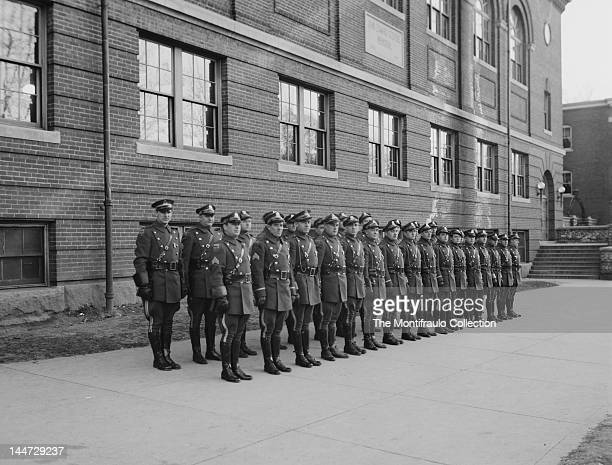Large group of American state police in full uniform on parade outside a police building on the wall of building is a memorial plaque to a John...