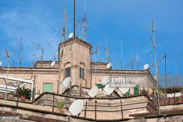 Large group of antenna and satellite dishes on rooftop, Italy