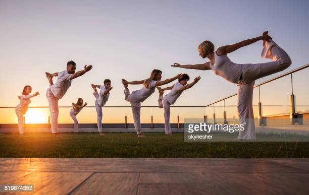 Large group of athletes doing Yoga balance exercises on a balcony at sunset.