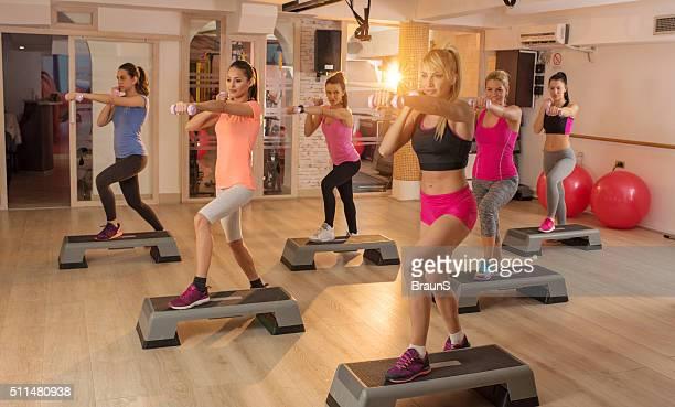 Grand groupe de étape athlètes exercice avec haltères.