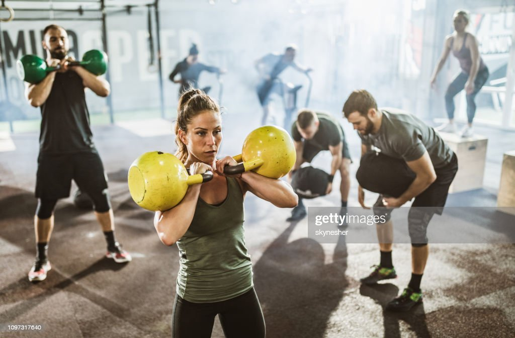 Large group of athletes exercising strength of cross training in a gym. : Stock Photo