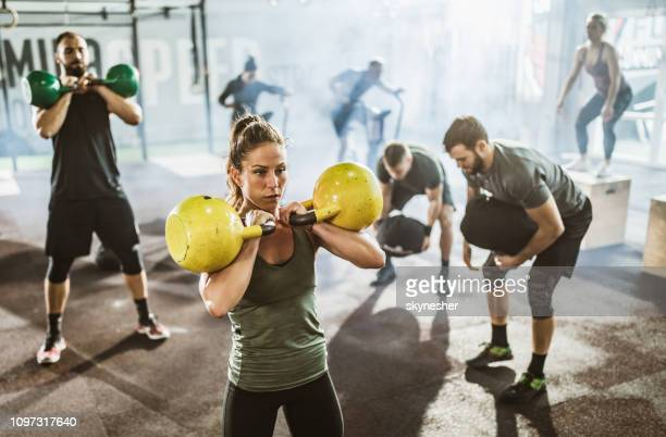 large group of athletes exercising strength of cross training in a gym. - circuit training stock photos and pictures