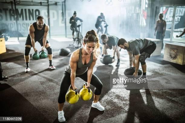 grande grupo de atletas exercitando a força da cruz treinamento em uma academia. - treinamento em circuito - fotografias e filmes do acervo