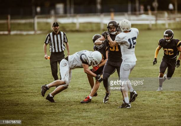 large group of athletes playing american football on a field. - american football judge stock pictures, royalty-free photos & images