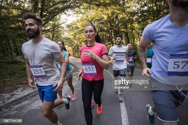 large group of athletic people taking part in marathon race. - half_marathon stock pictures, royalty-free photos & images