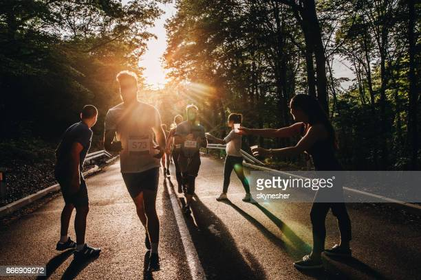 Large group of athletic people taking water at refreshment point during marathon race in nature.