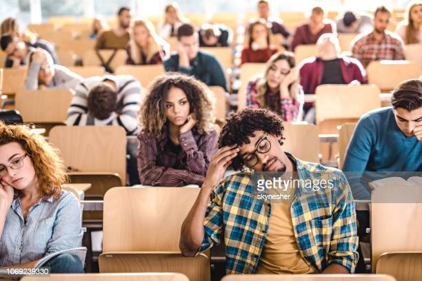 large group of bored college students in a lecture hall. - amphitheater stock photos and pictures