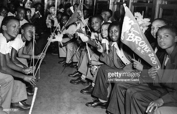 Large group of boys sitting in a subway carriage, holding Bronx Zoo pennants, New York, New York, 1960.
