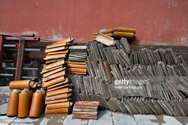 large group of brick and tiles in front of a red wall - hohhot - fotografias e filmes do acervo