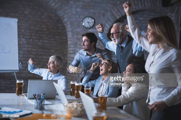 large group of business people cheering while watching a sports game in the office. - mens world championship stock photos and pictures