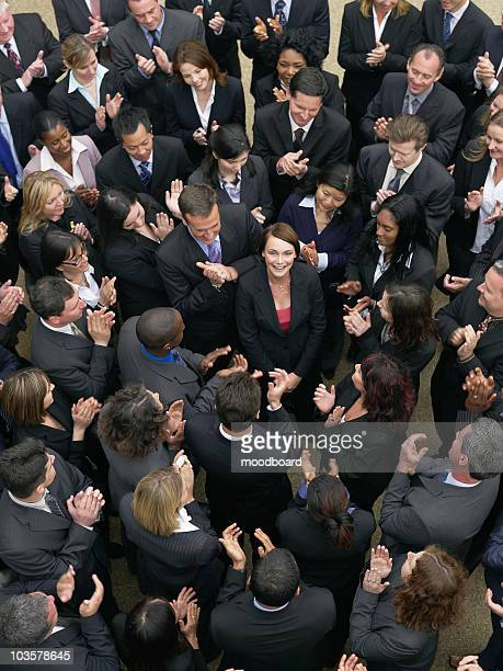 Large group of business people clapping, surrounding woman looking up, elevated view