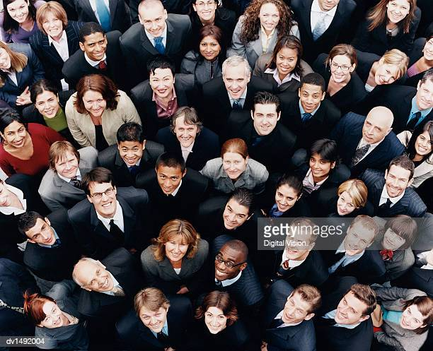 large group of business people standing and looking up at camera - large group of people stock pictures, royalty-free photos & images