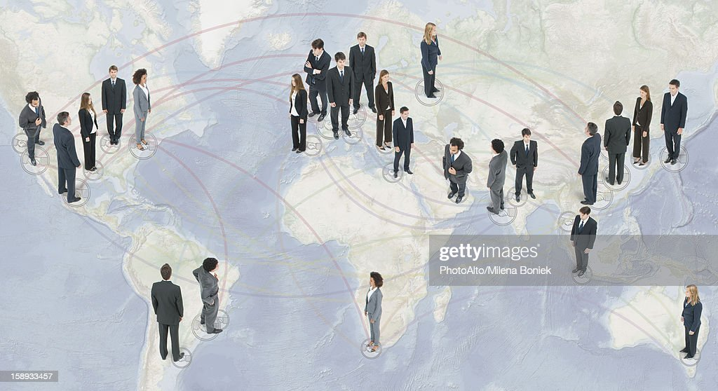 Large group of business people standing on world map : Foto de stock