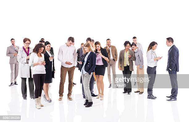 Large group of business people text messaging on smart phones.