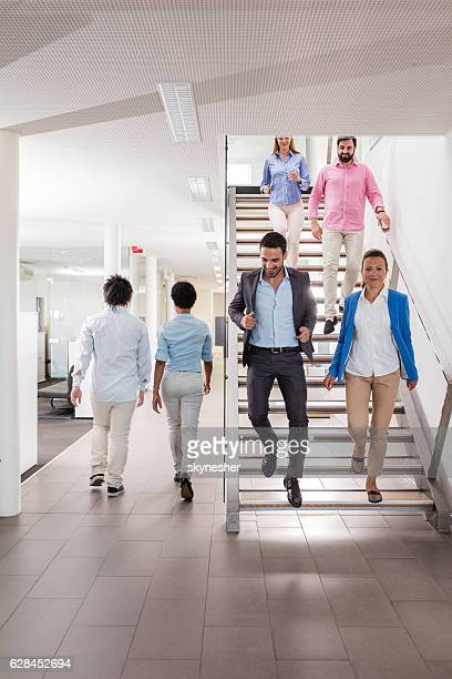 Large group of business people walking in a hallway.