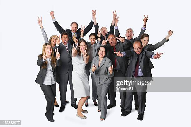 Large group of business people with victory sign against white background