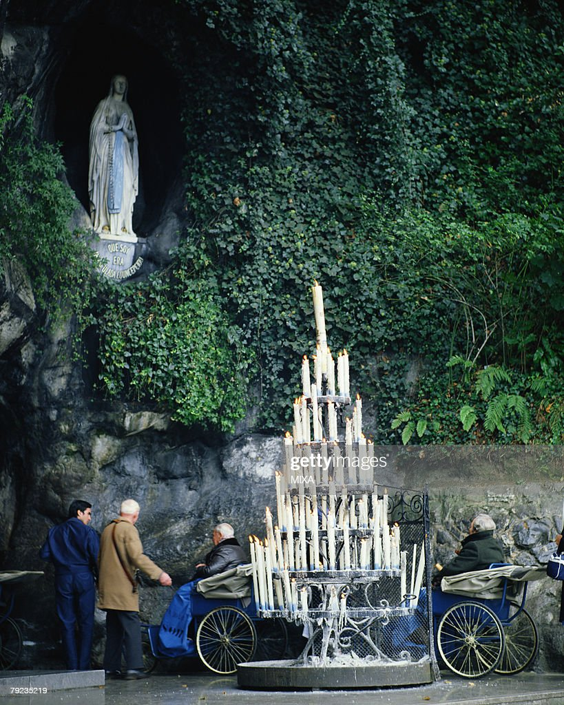 Large group of candles ignited near Virgin Mary in Lourdes, France : Stock Photo