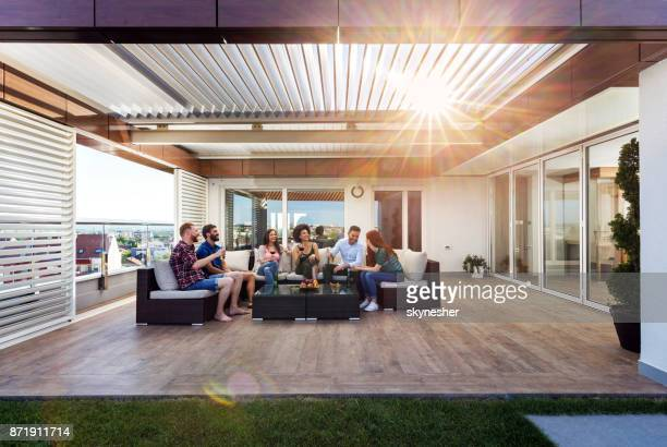 large group of carefree friends communicating on a penthouse patio. - patio stock pictures, royalty-free photos & images