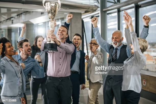 large group of cheerful business people celebrating success with a trophy in the office. - award stock pictures, royalty-free photos & images