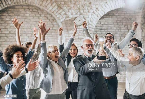 grande grupo de pessoas de negócios alegre com um troféu no escritório. - trophy - fotografias e filmes do acervo