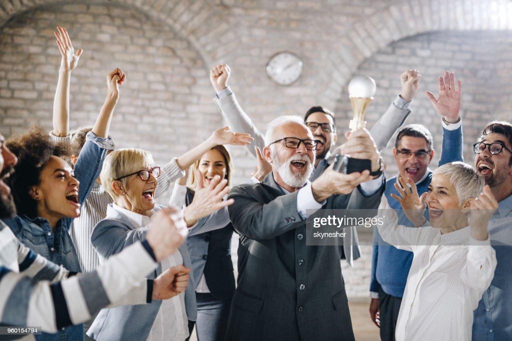Große Gruppe von fröhlichen Geschäftsleute mit einer Trophäe im Büro. : Stock-Foto