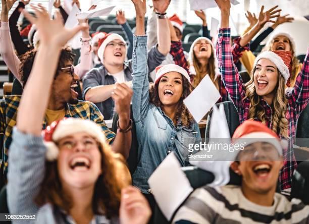 Grote groep van vrolijke studenten vieren Nieuwjaar in collegezaal.