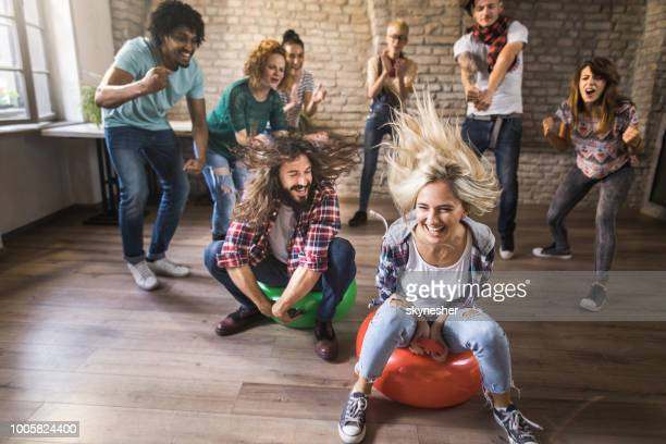 Large group of cheerful freelancers having fun during hoppity horse in casual office.