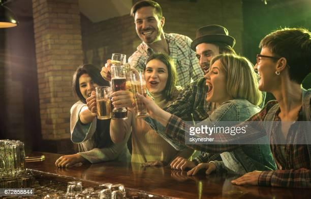 Große Gruppe von fröhlichen Freunden Toasten mit Bier in einer Bar.