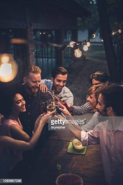large group of cheerful people having fun while toasting with alcohol on a night party. - cocktail stock pictures, royalty-free photos & images