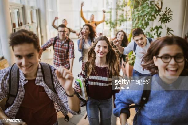große gruppe fröhlicher schüler läuft durch den schulflur. - schulkind stock-fotos und bilder